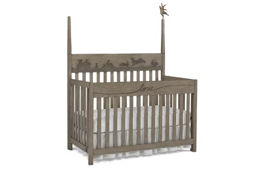 Warm grey baby crib with a dancing bunny on a spindle