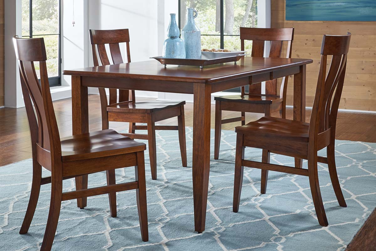 Warm cherry colored dining set made of solid wood with elegant curved chairbacks and tapered legs
