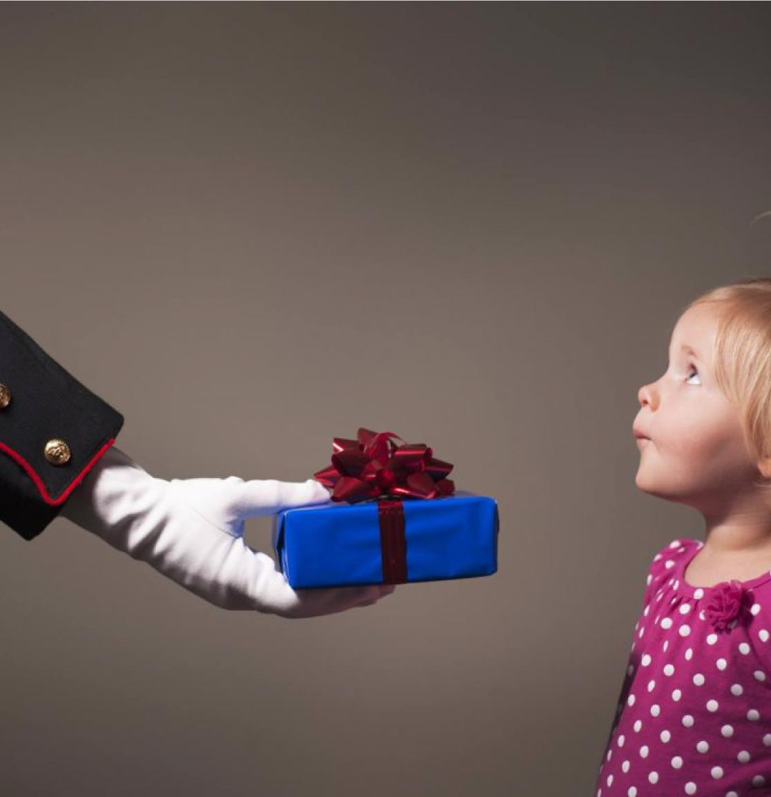 White-gloved hand beloning to a US Marine handing a gift to a little girl looking up at him