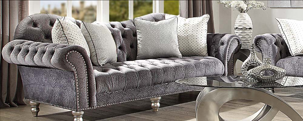 Ornate tufted grey sofa with patterned velvet fabric