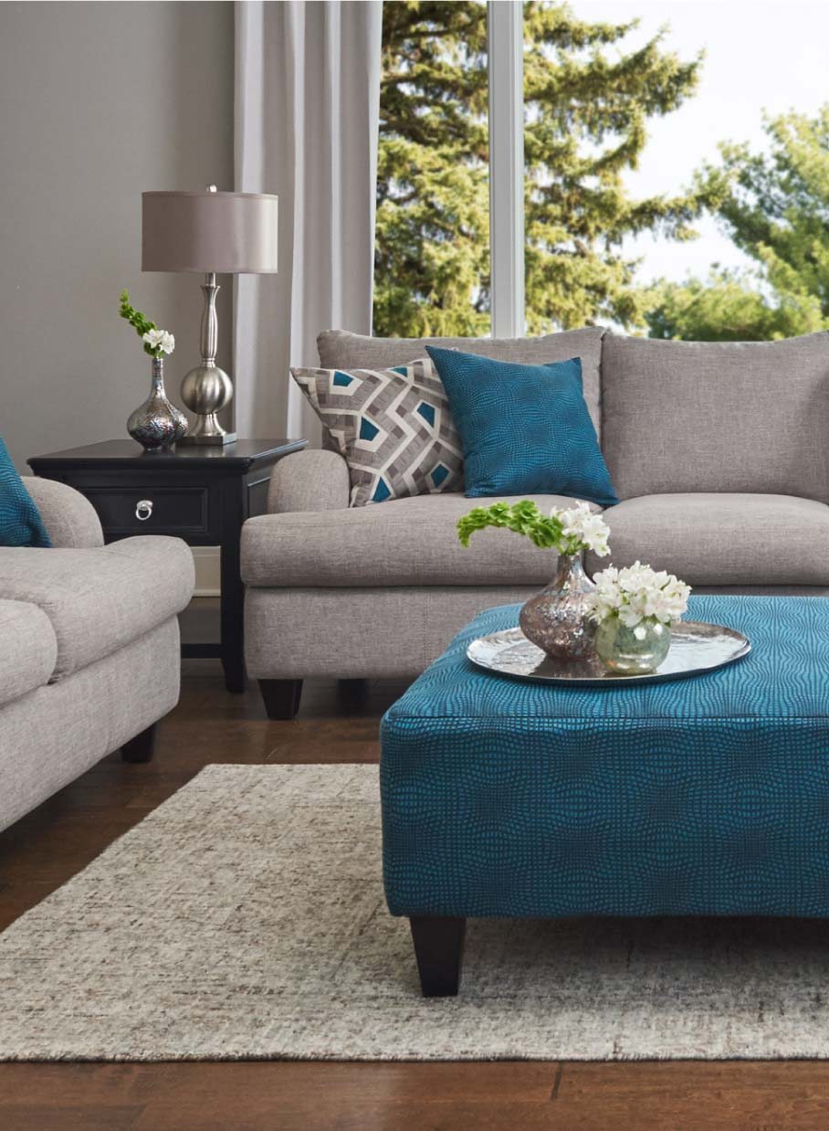 Contemporary sofa with English swoop track arms and teal accent pillows and ottoman