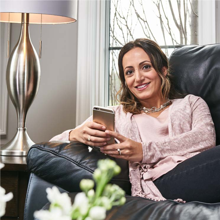 Fashionable woman on a leather reclining sofa with her iPhone plugged into it