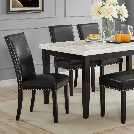 Round brown wood dining table with trestle base and matching chairs with white upholstery