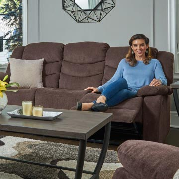 Brown reclining sofa with a model sitting on to display the reclining action.