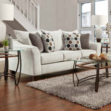 Light Grey sofa with swoop track arms and toss pillows in geometric patterns in neutral colors.