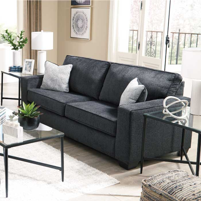 Warm grey sofa, loveseat, and matching chair in a room decorated in beige in grey colors with a solitary green indoor tree