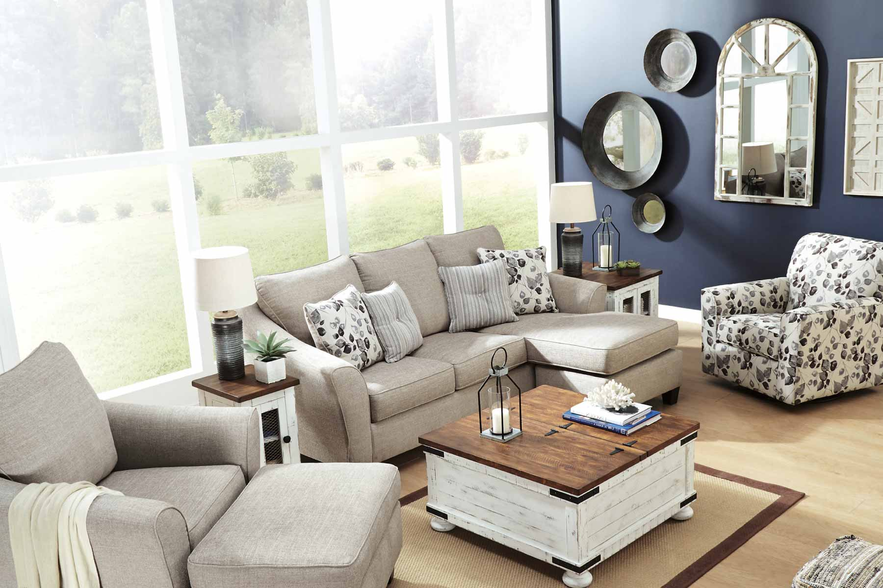 Abbey beige sofa with moveable chaise in front of a large window and muted blue wall.