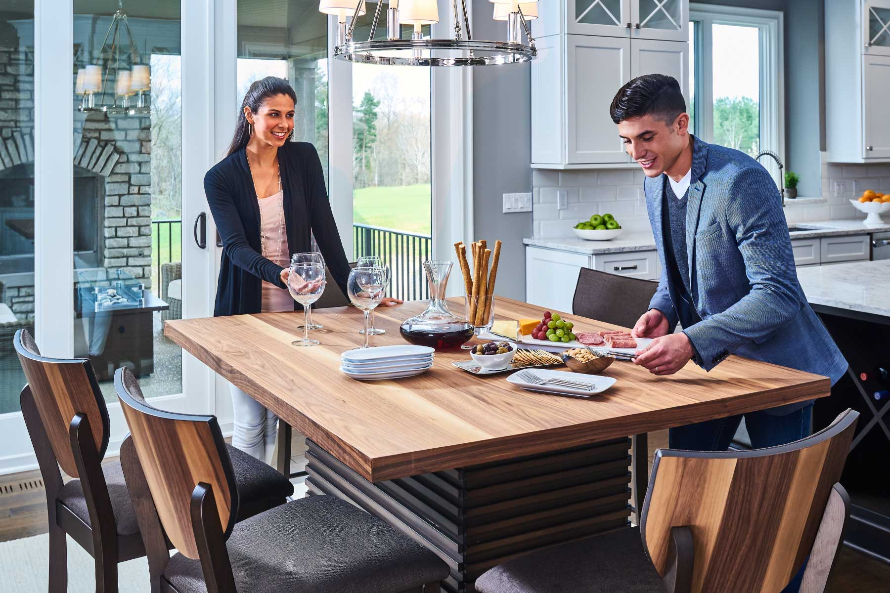 Young professional couple preparing for a dinner party around the Fleming counter-height dining set.