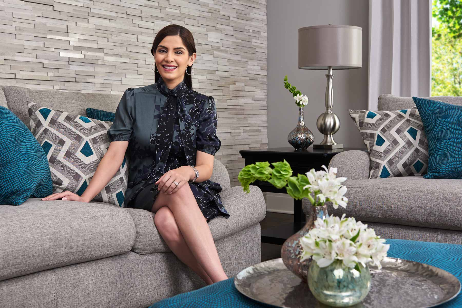 Woman sitting on grey contemporary sofa with teal accent pillows.