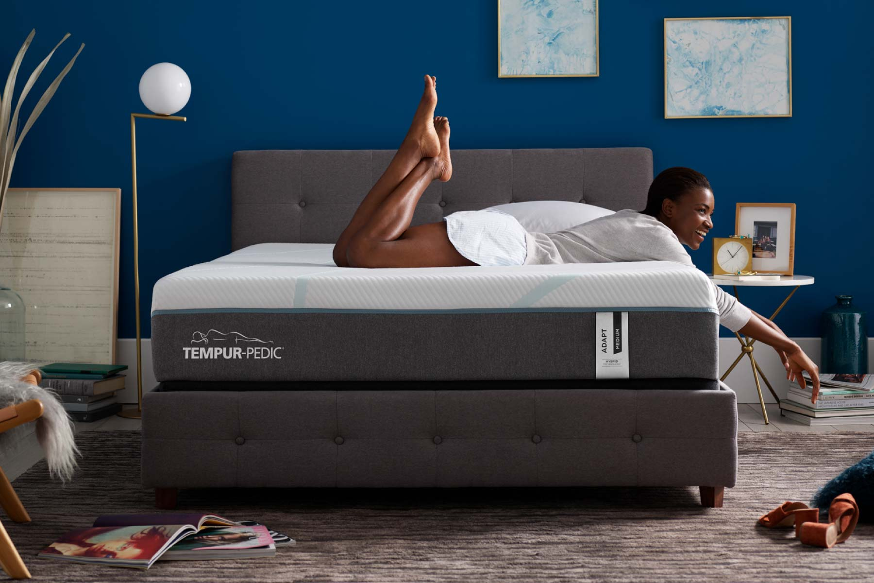 Young woman lounging over the side of a Tempur-Pedic Adapt mattress in a bedroom with a dark blue wall.