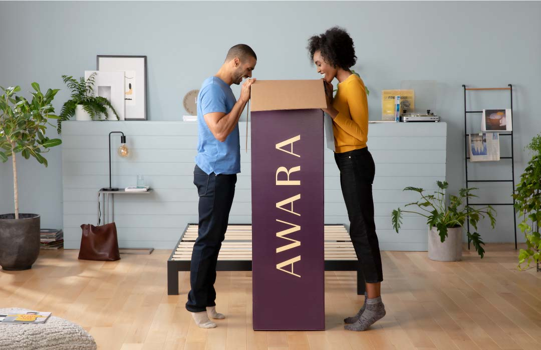 Couple looking into a tall box standing up with the Awara logo on the side