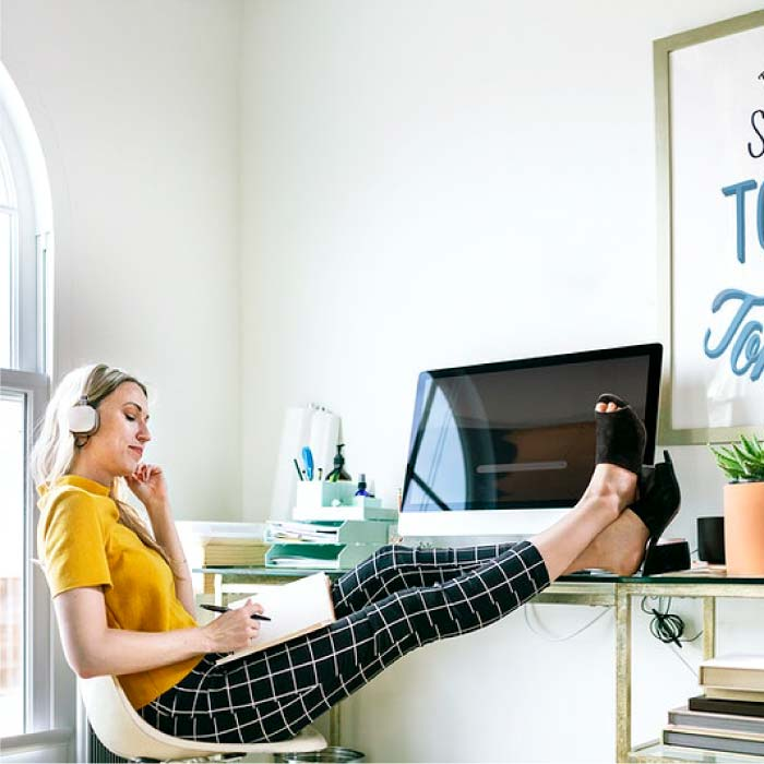 Woman with her feet up on the desk of her home office
