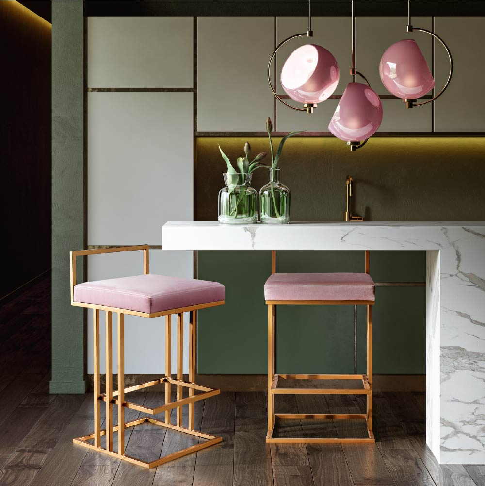 Dinette featuring pink upholstered stools with angular gold bases, round pendant lights and white marble counter