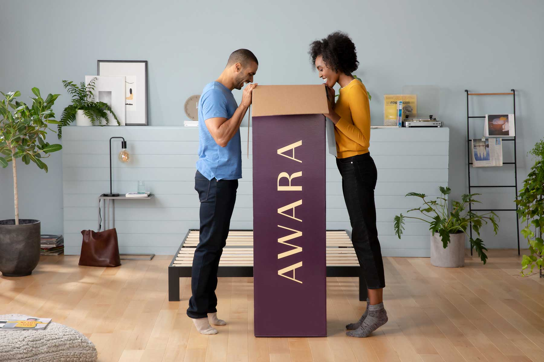 Couple peeking over the edge of a tall purple box with AWARA on the side