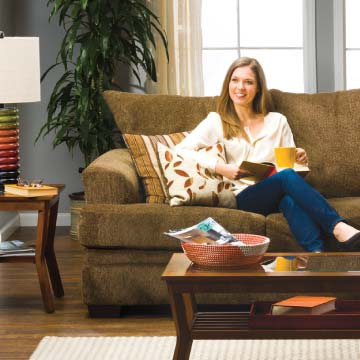 Woman sitting on brown sofa with t-cushions and decorative pillows.