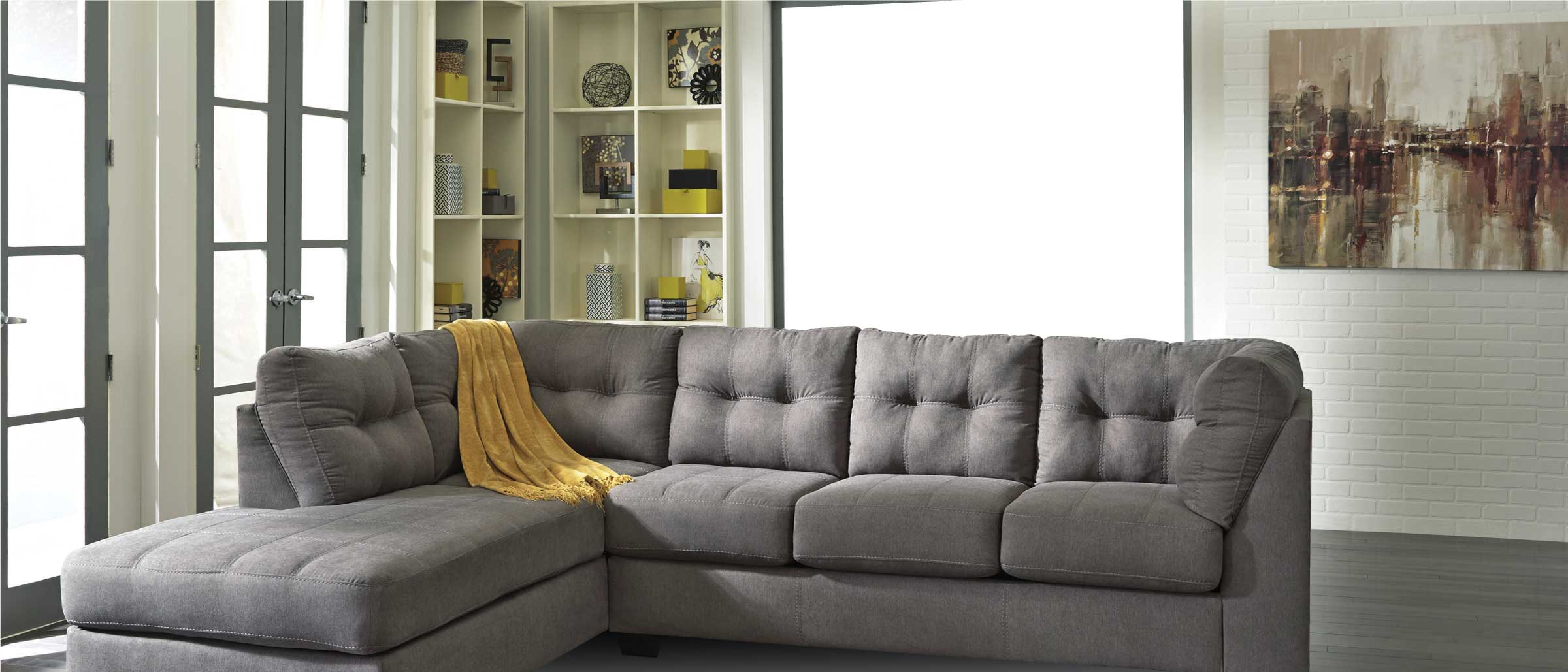 Contemporary grey sectional with tufted back and yellow throw in a living room with a brick wall